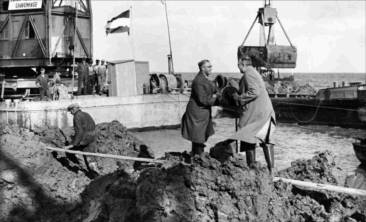 The mayor of Urk (right) and the mayor of Lemmer shake hands at the Lemmerkant, after the last soil had been deposited in the IJsselmeer, so that Urk is no longer an island and the drainage of the Noordoostpolder can begin, October 12, 1939.