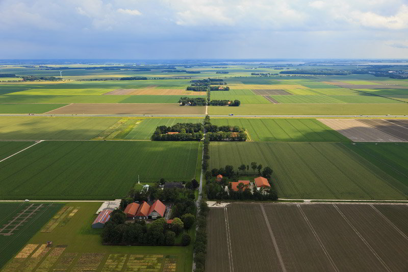 The typical polder landscape. Dead straight roads, large rectangular plots, farms with canals. Noordoostpolder, 30-06-2011; Johannes Postweg (intersected by the A6), Nagele right on the horizon.